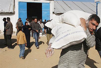 Gazan carries sacks of flour provided by UNRWA (Archive photo: AP)