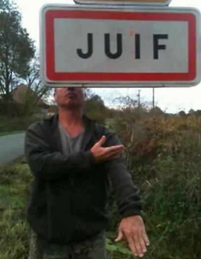 Under a sign reading 'Jew'