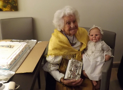 Oma Ella at her 104th birthday celebrations, holding a silver-bound Bible, a gift from the Tourism Ministry, and a handmade doll in her likeness, wearing the clothes in which she was christened (Photo courtesy of the Tourism Ministry)