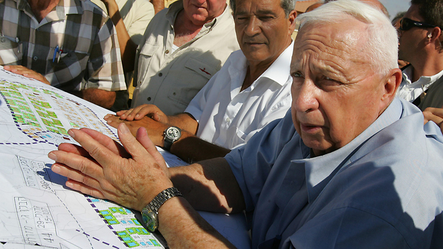 Sharon with housing plans for settlers to be evacuated from Gaza, July 2005 (Photo: Getty Imagebank)