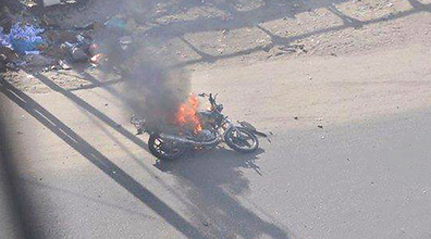 A burning motorcycle lies on the ground following the IAF strike