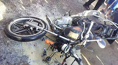 The motorbike ridden by the two lies on the ground