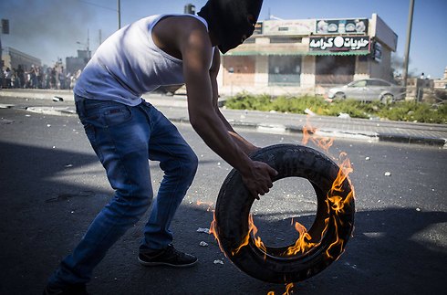 Masked Arab youth throwing a burning tire during clashes with Israel Police in East Jerusalem neighborhood of Shuafat (Photo: Gettyimages)