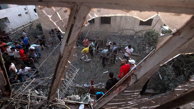 Residents examining the destruction caused by a Gaza rocket that hit a Hebron home (Photo: EPA)