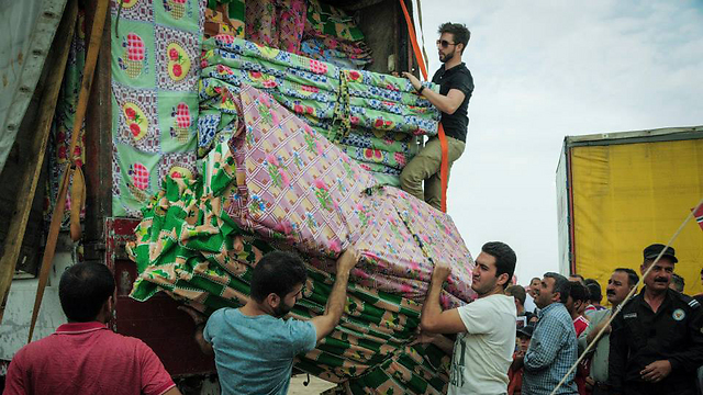Israeli aid workers distributing mattresses to Yazidi and Christian refugees who escaped Kobani (Photo: IsraAID)
