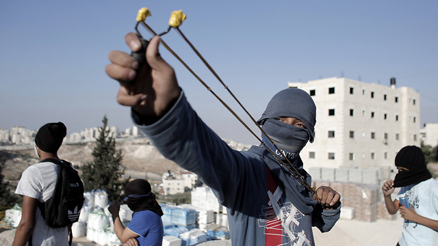 Palestinian uses sling to hurl stones in East Jerusalem (Photo: AFP)