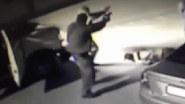 Video footage showing police officer pointing gun at Hamdan.