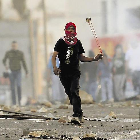 Palestinian uses sling to hurl stones in Kafr Kana (Photo: Gil Nechushtan)