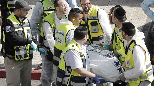 Removing a body from the scene of the attack. (Photo: AFP) (Photo: AFP)
