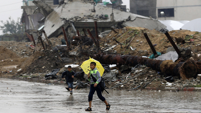 A child walks in Gaza - with an umbrella and sandals. (Photo: AFP) (Photo: AFP)