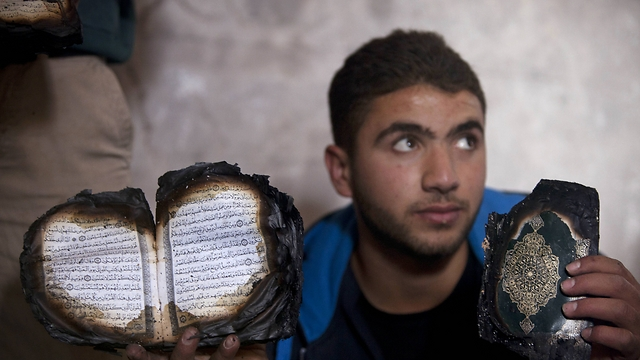 Resident of Mughayer holds up Koran and other artifact burned as a result of the mosque fire. (Photo: Associated Press) (Photo: Associated Press)