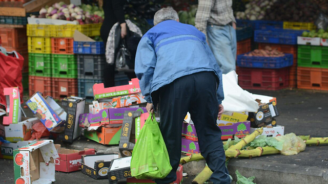 An elderly person searching for leftover food at the market in Haifa (Photo: Archive/George Ginsburg)