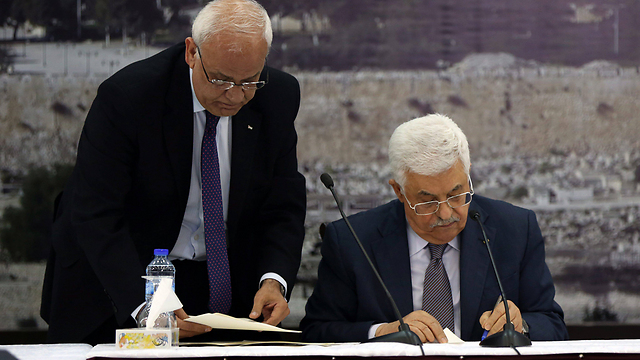 Abbas, accompanied by Erekat, signing requests to join international institutions in December (Photo: EPA) (Photo: EPA)