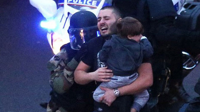A hostage carrying a child flees the siege at the Hyper Cacher.