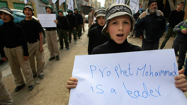 Lebanese child holds up protest sign (Photo: AP)