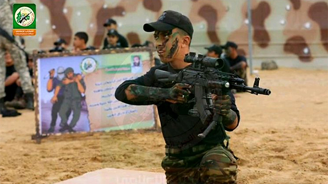 A young boy holds a n upgraded rifle at a Hamas camp