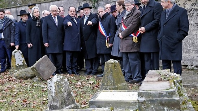 Hollande, center, with at his right, Israeli ambassador to France Yossi Gal, points to desecrated tombstones during a visit at Sarre-Union Jewish cemetery, eastern France (Photo: Associated Press) (Photo: Associated Press)