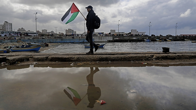 Man holds Palestinian flag at Gaza port. (Photo: Associated Press) (Photo: AP)