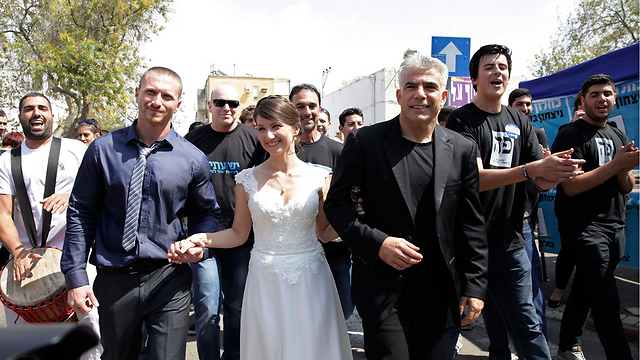 Yair Lapid catches up with the bride and her new spouse in Holon. (Photo: Reuters)