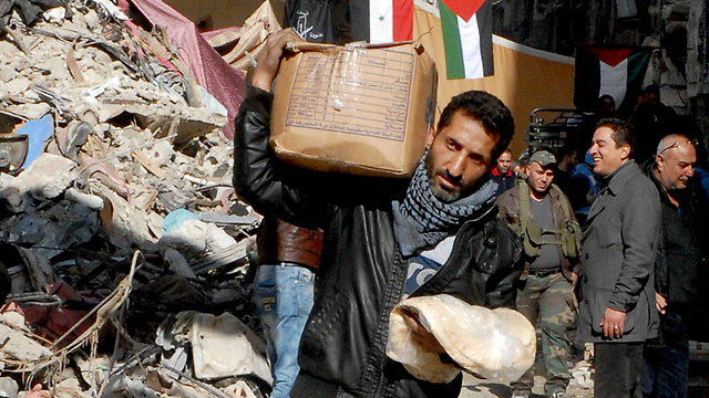 Refugees in Yarmouk receiving food aid, January 2014 (Photo: EPA)