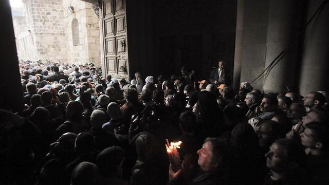 A Christian pilgrim holds up a candle as others gather at the church of the Holy Sepulcher (Photo: AP) (Photo: AP)