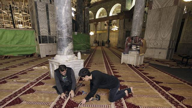 Workers place new carpets at the Dome of the Rock shrine in Jerusalem (Photo: AP)