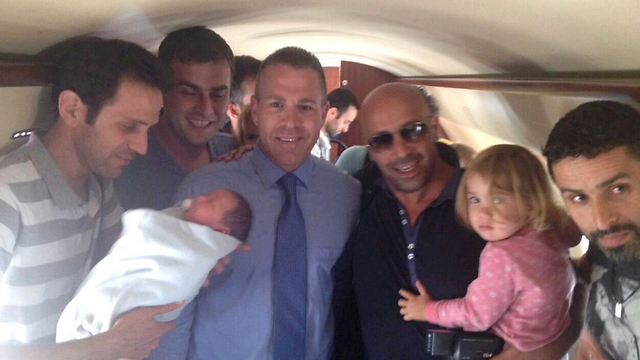 Interior Minister Gilad Erdan with Israelis who returned rom Nepal with surrogate babies.