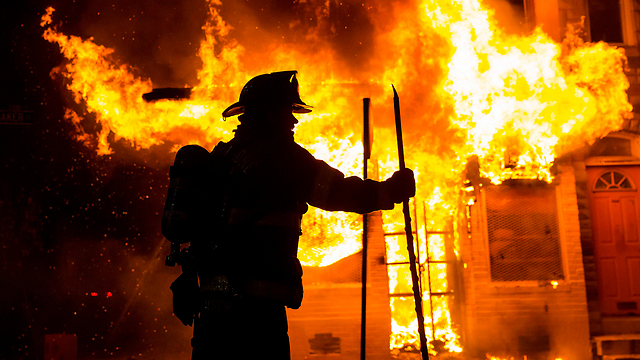 Firefighter near burning home (Photo: Reuters)