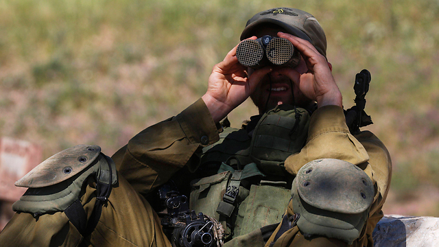 An IDF soldier on the Golan looks into the nearby Syrian town of Quneitra, the site of heavy fighting. (Photo: EPA)