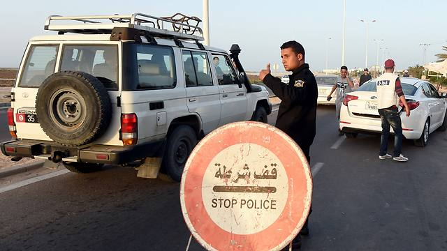 A Tunisian policeman controls cars at a checkpoint on the road to the tourist area in Houmt Souk (Photo: AFP)