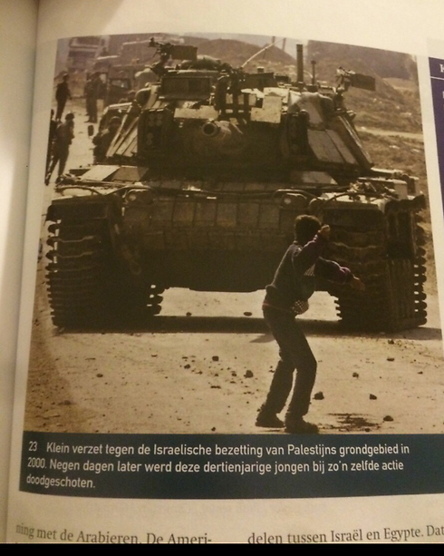 Page with photo showing boy throwing stone at tank