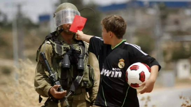 Palestinian boy showing an Israeli soldier a red card