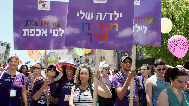 Marchers walk with signs saying: 'My child, only your way' and 'boy or girl, who cares' (Photo: Ido Erez)