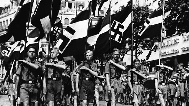 In this Feb. 24, 1936 file photo, a group of boys march beneath Nazi standards in Berlin (Photo: AP)