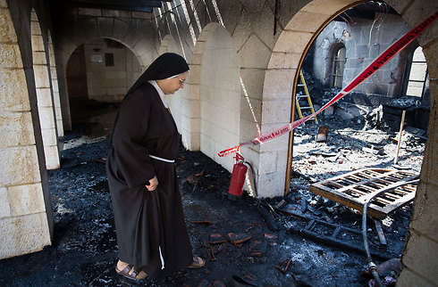 Nun inside the heavily damaged church after the fire (Photo: AFP)