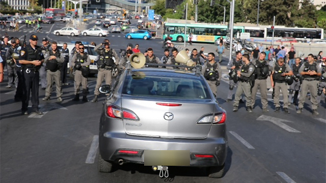 Large police forces look on as protesters block a major road (Photo: Motti Kimchi)