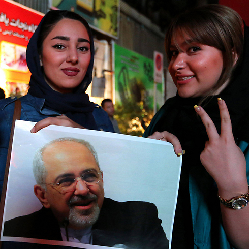 Iranians celebrating with a picture of President Hassan Rouhani (Photo: AFP)