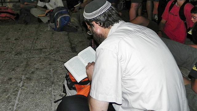 Jews praying while sitting on the floor during Tisha B'Av (Photo: Ziv Reinstein)