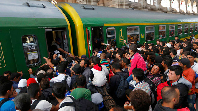 Refugees rush at train in Budapest, Hungary (Photo: Reuters)