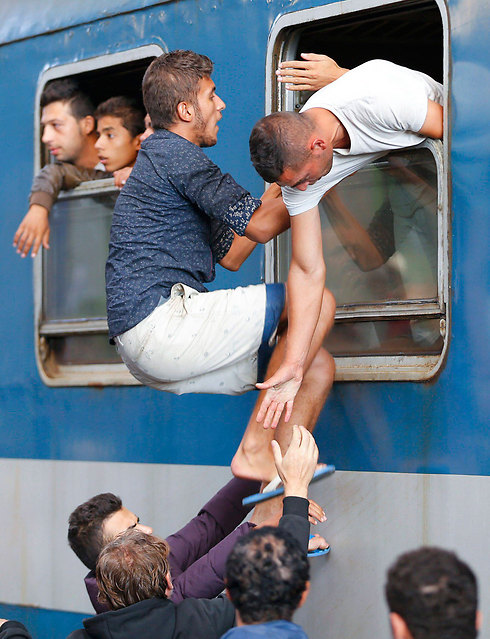 Refugees trying to get on a train in Budapest (Photo: Reuters)