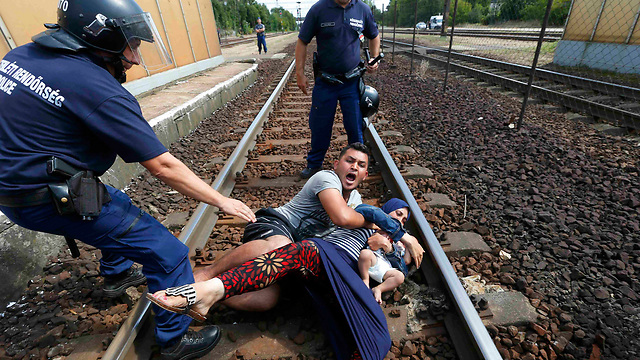 Police wrestle family protesting being taken to nearby refugee camp in Bicske, Hungary on Thursday (Photo: Reuters)