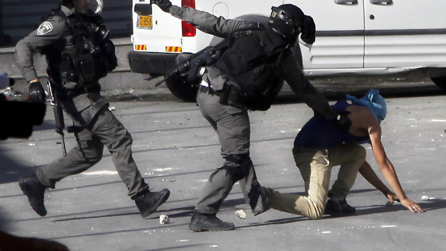 Security forces try to apprehend suspect during riots in Shuafat (Photo: AP)