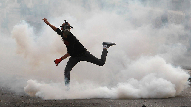 A young Palestinian demonstrator throws back tear gas that was fired by the IDF in Bethlehem (Photo: AFP)