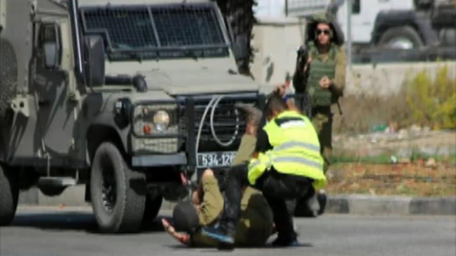 The Palestinian attacker stabbing a soldier on the ground.