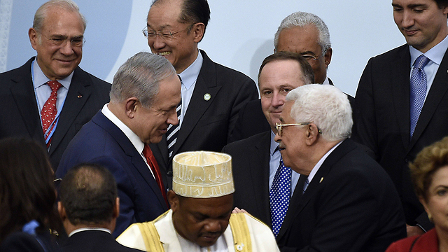 PM Benjamin Netanyahu and PA President Mahmoud Abbas meet at the 2015 UN Climate Change Conference (Photo: AFP)