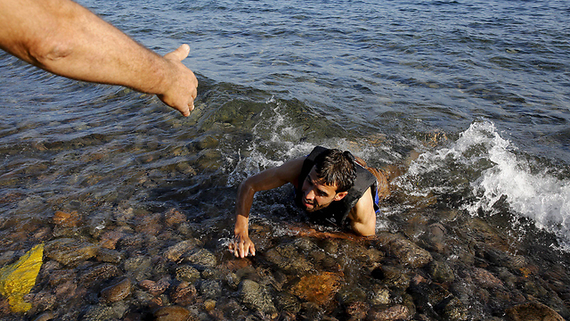 An aid worker reaches for a Syrian refugee on the coast of Lesbos (Photo: Reuters)