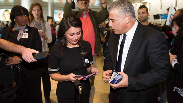 Yesh Atid head Yair Lapid at Ben Gurion Airport with Israelis about to fly abroad, distributing booklets on how to fight BDS. (Photo: Ido Erez)