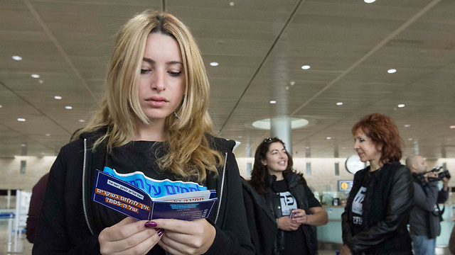A traveler reading a new booklet on how to answer back to BDS claims (Photo: Ido Erez)