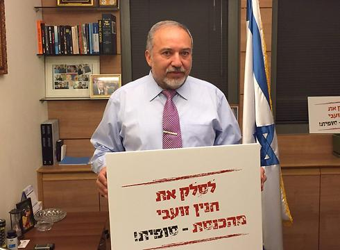 Lieberman holding a sign calling to 'Kick Haneen Zoabi from the Knesset - for good!'