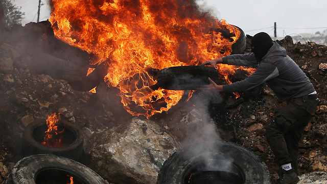 Palestinian burning tires during rioting near Nablus this month (Photo: AFP)